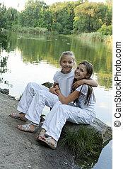 Two girls play at the lake