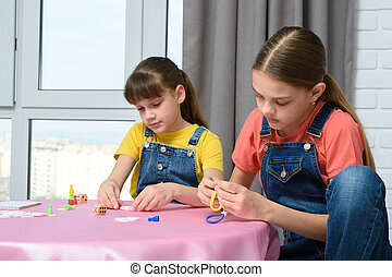 Two girls play games at the table