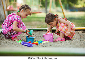 Two girls play in the sandbox at the playground