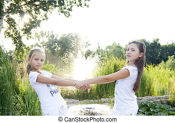 Two girls play with flowers in park