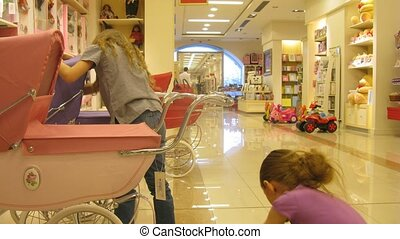 Two girls play with toy carriages for dolls in shop, time lapse