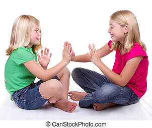 two girls playing clapping game, white background
