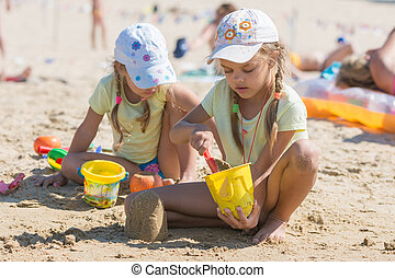 Two girls playing in the sand on the beach
