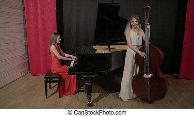 Two girls playing musical instruments. Piano and doublebass