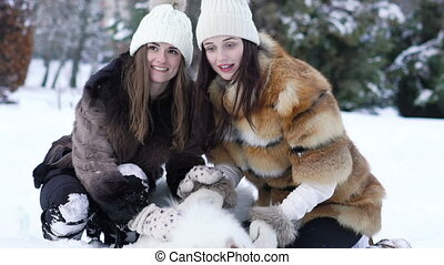 Two girls playing with white husky dog in snow . Slow motion
