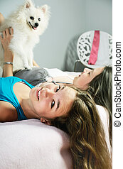two girls playingwith a Pomeranian on the bed close-up....