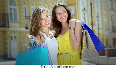 Two girls pleasing and posing while holding shopping bags with fashion