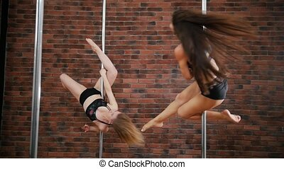 Two girls practicing a pose in a pole fitness class on the...