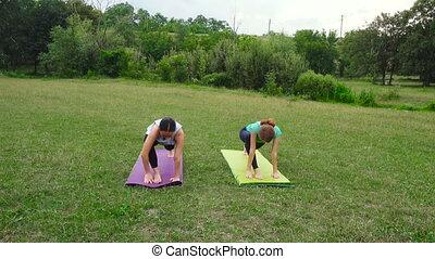 two girls practicing yoga exercises