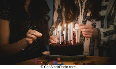 Two girls prepare birthday cake with candles. Surprise party...