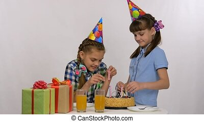 Two girls put candles in a birthday cake