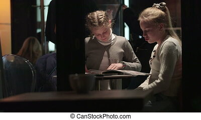 Two girls reading menu at cafe view from outside