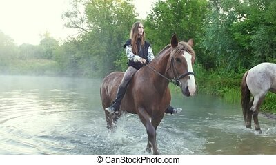 Two girls riding horses out of the water early in the...