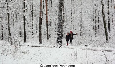 Two girls run closer in woods where all covered with first...