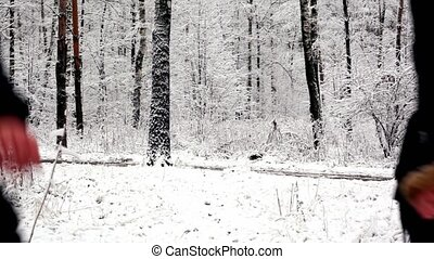 Two girls run into woods where all covered with snow, on the...