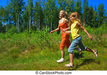 Two girls running on a meadow
