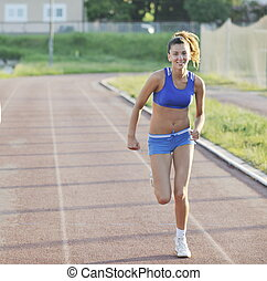 two girls running on athletic race track - young girl...