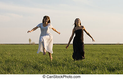 Two girls running on the field