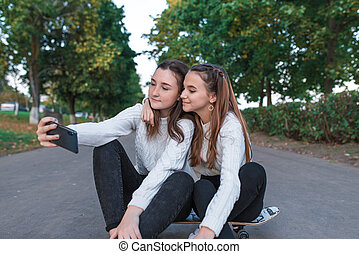 Two girls schoolgirls 13-16 years old, taking pictures phone, summer in city park, background trees fall, sweaters jeans, skateboard. Online call application on Internet. Video call on smartphone.