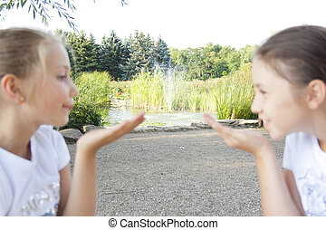 Two girls send air kisses