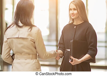 Two girls shaking hands in modern office, smiling and looking at each other on a sunny day