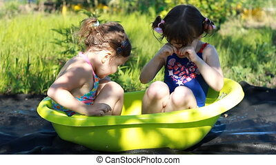 Two girls sisters bathe in water, play, laugh and have fun....