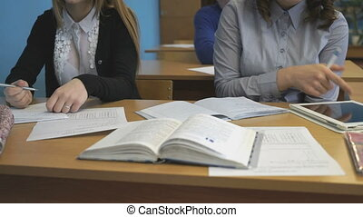 Two girls sit at a desk and write in notebooks