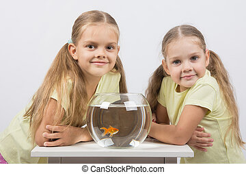 Two girls sit at a round aquarium with goldfish and look in the frame