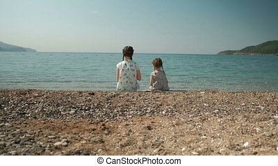 Two girls sit on shore and throw stones into water in summer day outdoors.