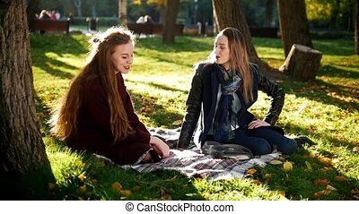 two girls sit on the blanket at the park
