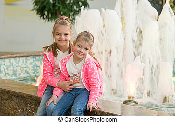 Two girls sitting at the fountain in the mall and joyfully look to the Frame