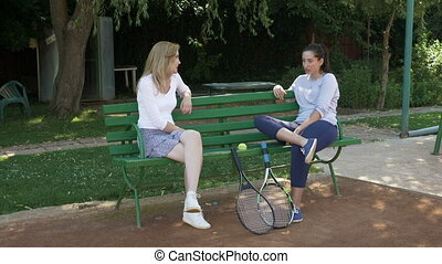 Two girls sitting on a bench chatting and resting with their tennis rackets near
