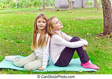 Two girls sitting on grass