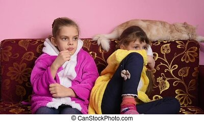 Two girls sitting on the couch and watching TV enthusiastically