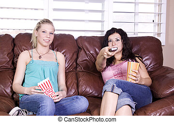Two Girls Sitting on the Sofa Watching a Movie