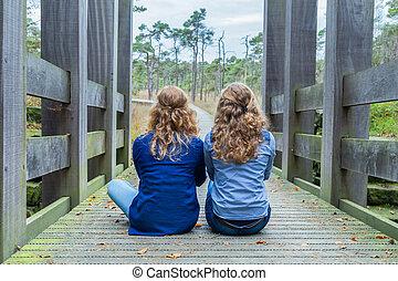 Two girls sitting on wooden bridge in nature