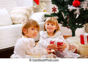 Two girls sitting with presents near Christmas tree