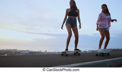 Two girls skateboarder rides on a Board on the slope against the sky from the mountain. Slow motion steadicam