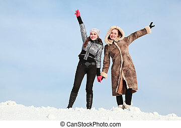 Two girls stand alongside  hold on  hands and lift free hand upwards