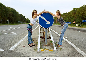 Two girls stand on a road