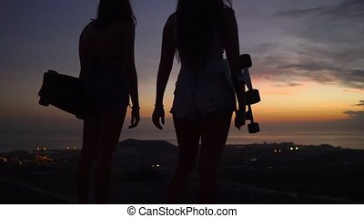 Two girls standing on the edge of the road with skateboards in their hands watching the sunset