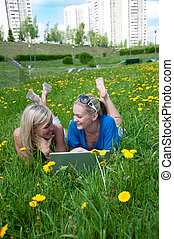 Two girls student with a laptop in the park