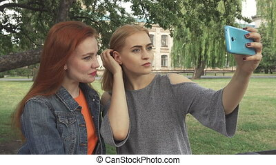 Two girls taking a selfie outdoors