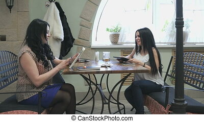 Two girls talking in a cafe and drink coffee