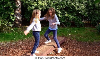 two girls teetering on an unstable log, playing in the park. active games and walks in the fresh air with children.