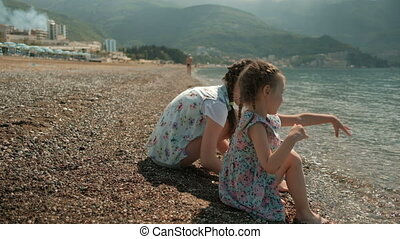 Two girls throw stones in water sitting on beach in summer.