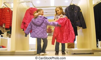 Two girls try on jackets in shopping center, time lapse
