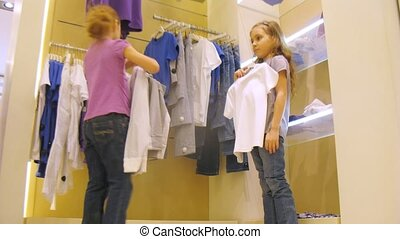 Two girls try on vest and shorts in shop, time lapse