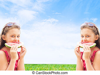 two girls twins eating watermelon on blue sky background