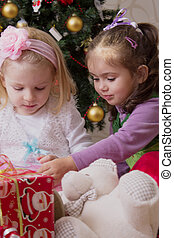 Two girls under Christmas tree